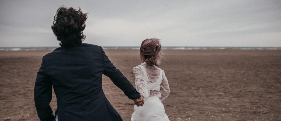 echtpaar-rent-in-trouwkleren-op-strand