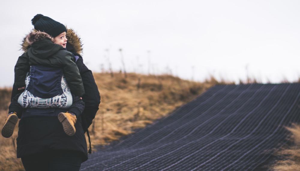 Moeder loopt met kind op rug